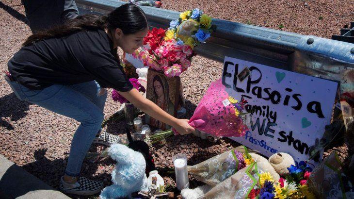 Una mujer deja flores en homenaje a las víctimas del tiroteo de El Paso.