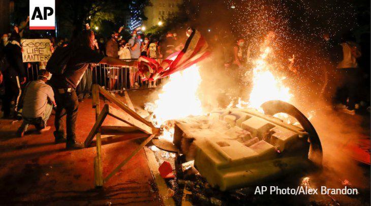 Un hombre quemando la bandera de Estados Unidos en medio de una manifestación.