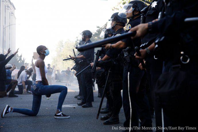 Manifestantes arrodillados en medio de una protesta.