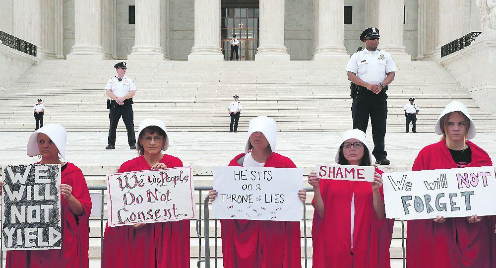 """ÉL NO. """"Se sienta en un trono de mentiras"""" y """"no olvidaremos"""" fueron lemas en la protesta estilo El cuento de la criada contra Kavanaugh."""