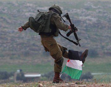 Un soldado israelí patea una bandera palestina durante una manifestación en Cisjordania.
