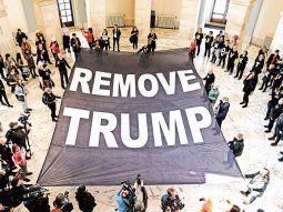 Presión. Un grupo de manifestantes desplegó dentro del edificio del Senado de EE.UU. una bandera que pide la destitución de Donald Trump.