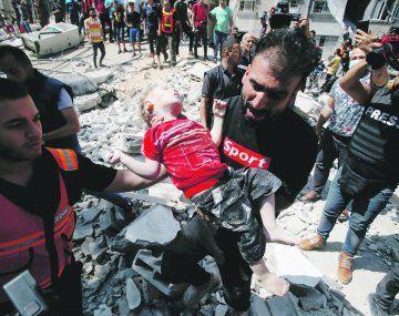 DERRUMBE. Rescatistas extraen el cuerpo de un niño sin vida debajo de los escombros. Unos 800 palestinos heridos han sido evacuados hacia Egipto.