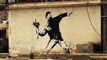 La obra Love is in the Air, de Banksy, será subastada por Sothebys-