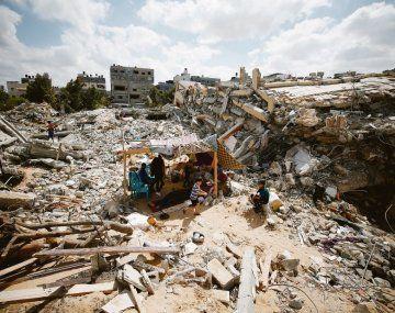 DESOLACIÓN. Once días de guerra y fuertes ataques israelíes dejaron sólo devastación en la Franja de Gaza. En la foto, un grupo de palestinos se cobijan bajo una tienda improvisada sobre los restos de su casa destruida.