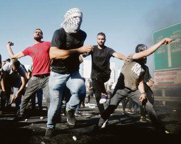 TENSIÓN. Un grupo de jóvenes arrojan piedras contra soldados israelíes en Cisjordania. La protesta tuvo lugar días después de que se registraran violentos choques en las ciudades mixtas de Israel.