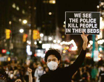 """RESISTENCIA. Las marchas contra el racismo institucional son una constante desde principios de año en Estados Unidos. Un joven sostiene una pancarta en la que se lee """"vemos a policías matar gente en sus camas"""", en referencia al caso de Breonna Taylor."""